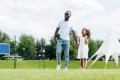 afro-amerikai rendőr fegyver és a lánya kezét, és séta, vidámpark