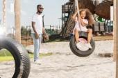 Fotografie afroamerikanischen Vater stand in der Nähe lächelnd Tochter auf Reifenschaukel im Freizeitpark