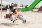 Fotografie african american father touching daughter cheek on spider web nest swing at amusement park