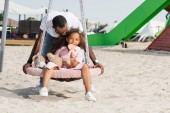 Fotografie african american father pushing happy daughter with lollipop on spider web nest swing at amusement park