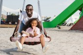 Fotografie smiling african american father pushing daughter on spider web nest swing with lollipop at playground