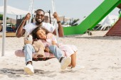 happy african american father and daughter on spider web nest swing at amusement park