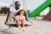 Fotografie african american father pushing daughter on spider web nest swing with lollipop at amusement park