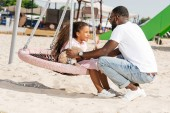 Fotografie african american father squatting near daughter on spider web nest swing at amusement park