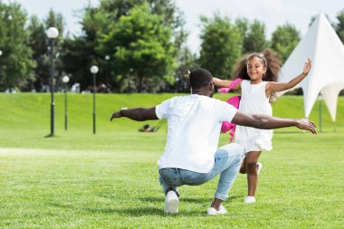 african american daughter with school bag running to father with open arms in park