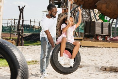 african american daughter showing two fingers on tire swing at amusement park