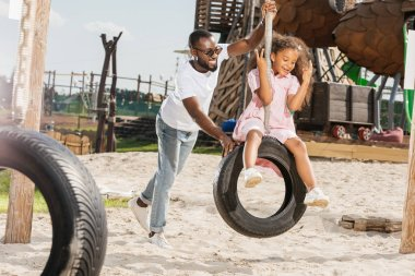 african american father and daughter on tire swing having fun on playground