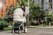 beautiful mother looking in baby stroller on street