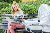 freelancer working with laptop on bench and holding baby stroller in park