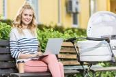s úsměvem sedí s notebookem na lavici poblíž dětský kočárek v parku a při pohledu na fotoaparát na volné noze