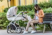 práce s notebookem na lavici poblíž dětský kočárek v parku a kávu v pohárek na volné noze
