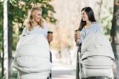 šťastné matky s kočárky a kávu v papírových kelímků v parku