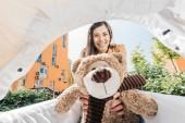 happy mother holding teddy bear in baby stroller