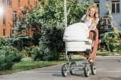 beautiful mother walking with baby stroller on street