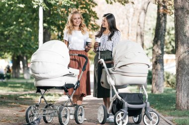 smiling mothers holding coffee to go and walking with baby strollers in park