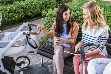 smiling mothers sitting on bench near baby strollers with coffee in paper cup and digital tablet