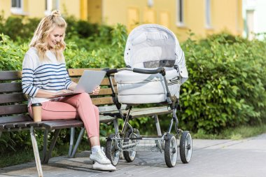 smiling freelancer working with laptop on bench near baby stroller in park