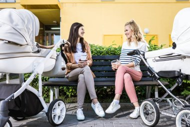 smiling mothers sitting on bench with coffee to go near baby strollers