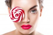 attractive young woman holding red lollipop in front of eye, isolated on white