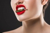 Fotografie cropped view of aggressive woman holding bullet in teeth, isolated on grey