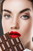 Fotografie attraktives Mädchen mit roten Lippen Essen Schokoriegel, isoliert auf grau