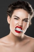 attractive aggressive girl holding dollar banknote in teeth, isolated on grey