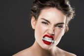 attractive angry woman holding money in teeth, isolated on grey