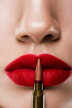 cropped view of girl holding bullet near red lips, isolated on grey