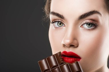 Attractive girl eating sweet chocolate bar, isolated on grey stock vector