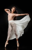 mladá žena baletku v bílé sukni pózuje na tmavé pozadí