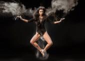 Photo beautiful ballerina in black bodysuit jumping on dark background with talc powder around