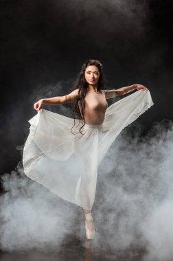 Beautiful young ballerina in white skirt dancing on dark background with smoke around stock vector
