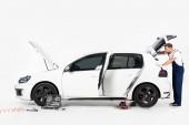 boční pohled hezký auto mechanik při pohledu do otevřeného kufru na bílém