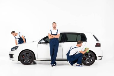 handsome auto mechanic cleaning car and standing near car after repairing on white