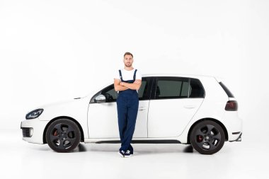 handsome auto mechanic leaning on car with crossed arms and looking at camera on white