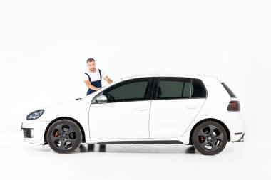 handsome auto mechanic cleaning white car on white