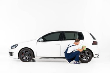 auto mechanic squatting and cleaning car after repairing on white
