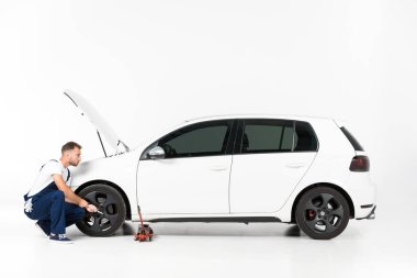 side view of auto mechanic changing car tire on white
