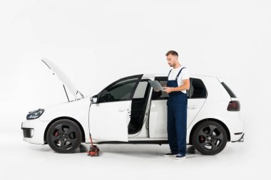handsome auto mechanic in blue uniform using laptop near broken car on white