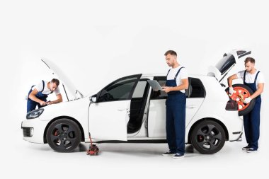 auto mechanic taking car tire, using laptop and looking in open car hood on white