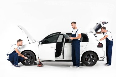 auto mechanic changing car tire, using laptop and looking in open car trunk on white