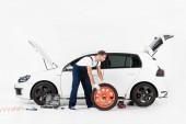 boční pohled na Automechanika v modré uniformě měnící se auto pneumatiky na bílém