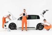 Fotografie auto mechanik mění auto pneumatiky, znázorňující tabletu a hledání v otevřené auto kapuce na bílém