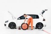 auto mechanik tlačí auto pneumatiky na bílém