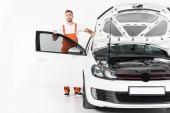 hezký auto mechanik stojící poblíž auto s otevřenou kapotou a dveře na bílém