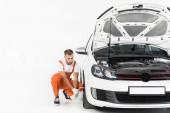 auto mechanik mění auto pneumatiky s otevřenou kapotou na popředí