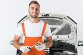 Fotografie smiling handsome auto mechanic holding monkey wrench near car on white