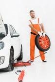 Fotografie auto mechanic in orange uniform carrying car tire on white