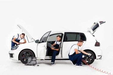 handsome auto mechanic inflating tire, using laptop and looking in hood on white