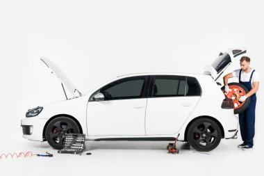 auto mechanic taking tire from car trunk on white